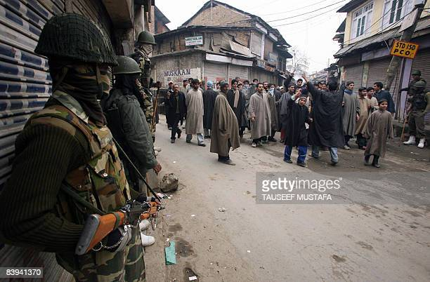 Indian Kashmiri demonstrators chant slogans as Indian Central Reserve Police Force personnel stand guard in Sopore some 50 kms north of Srinagar on...