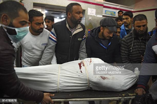 Indian Kashmiri men carry the body of a slain police officer inside a hospital in Srinagar on February 6 2018 Two gunmen opened fire on February 6 in...