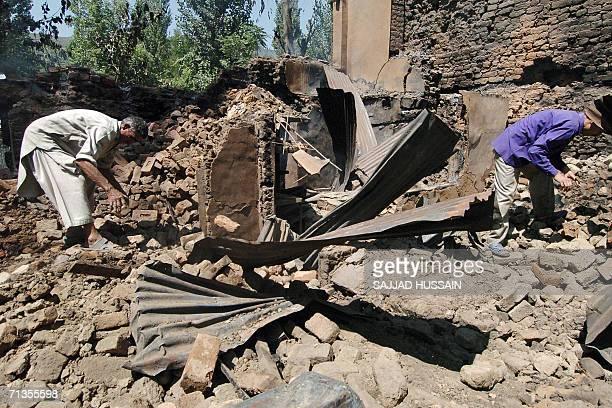 Indian Kashmiri men search for their belongings in the courtyard of their destroyed house in the northern Bandipora town 03 July 2006 Indian troops...