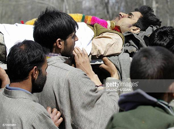 Indian Kashmiri Muslim men carry the body of a militant who was killed during an encounter with the Indian army during his funeral at Pampore south...