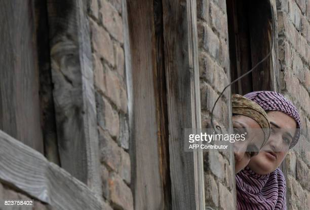 Indian Kashmiri residents look out of a window in Srinagar on July 28 2017 Authorities imposed restrictions on movements in Srinagar as a...