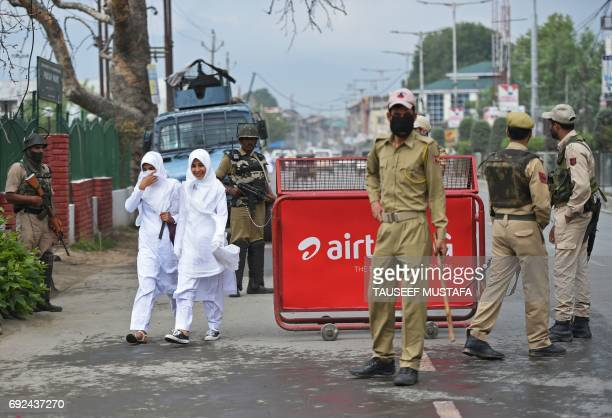 Indian Kashmiri students walk past Indian government forces standing guard in central Srinagar on June 5, 2017. Indian paramilitary forces killed...