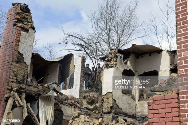 TOPSHOT Indian Kashmiri villagers look on next to the debris of a house after a gunbattle between suspected militants and government forces in the...