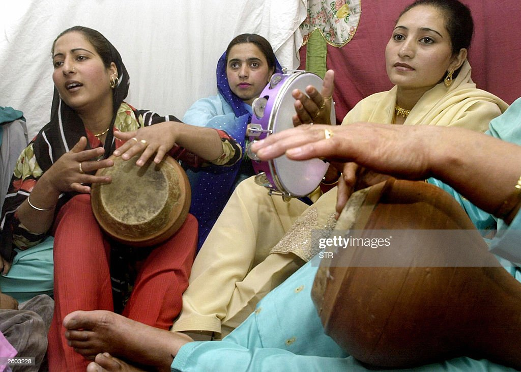Indian Kashmiri Women Play Traditional Drums As They Sing Songs During A Wedding Ceremony In Srinagar