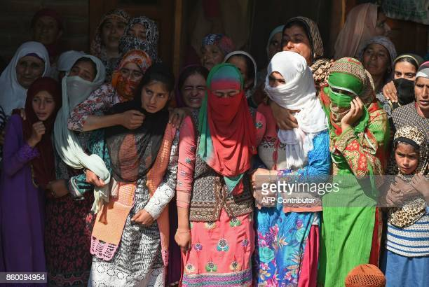 Indian Kashmiri women watch the funeral procession of slain militant Nasarullah Mir at Hajin village in Bandipora district north of Srinagar on...