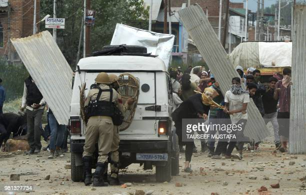 TOPSHOT Indian Kashmiri youths clash with Indian government forces on the outskirts of Srinagar on June 22 following a gun fight in southern Kashmir...