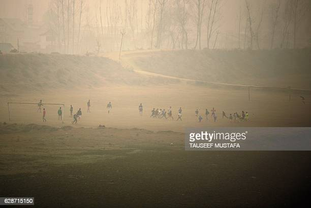 TOPSHOT Indian Kashmiri youths play football on a cold and foggy day in Srinagar on December 9 2016 The cold wave further tightened its grip in Jammu...