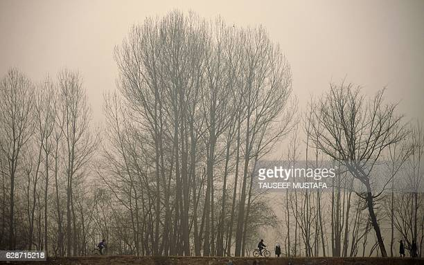 Indian Kashmiri youths ride bicycles on a cold and foggy day in Srinagar on December 9 2016 The cold wave further tightened its grip in Jammu and...