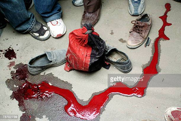 Indian Kashmiris stand beside a rivulet of blood on the road during a demonstration following an incident involving a speeding security forces...