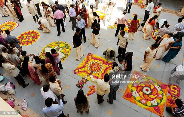 Indian Keralites prepare floral rangoli known as 'Pookkalam' as a part of Onam celebrations at Narayan Guru Vidhyalaya in Ahmedabad on September 13...
