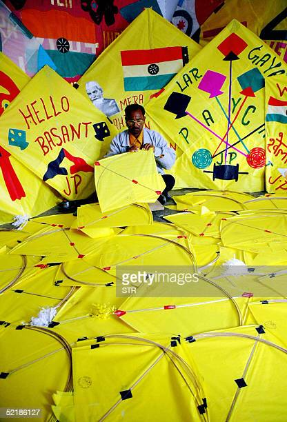 Indian kitemaker Jagmohan Kanojia puts the final touches to his kites on sale in his shop in Amritsar 12 February 2005 on the eve of the Basant...