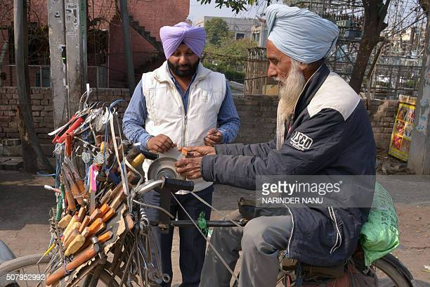 Indian knife sharpener Ajit Singh works on a knife on a sharpener hooked up to his bicycle in Amritsar on February 2 2016 Singh earn around 300...