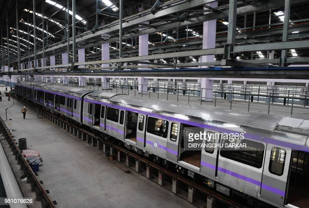 Indian Kolkata Metro Rail Corporation workers stand alongside new EastWest Metro carriages during a preview for the new trains at a workshop in...