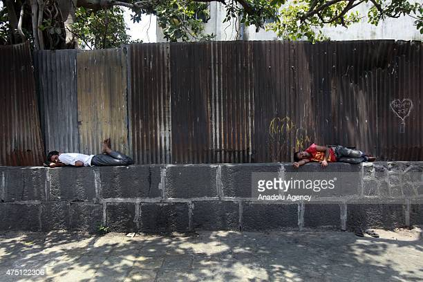 Indian laborers lie on a wall at a hot day in Mumbai on May 29, 2015. At least 1400 people have died in a major heatwave that has swept across India,...