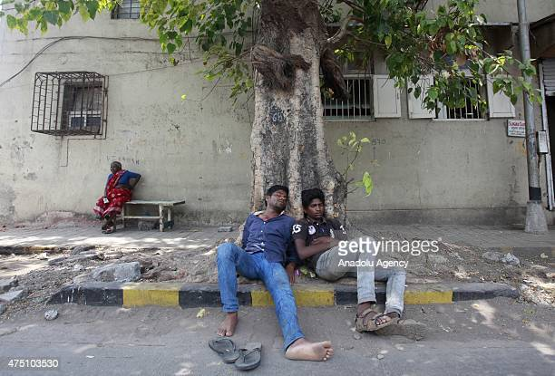 Indian laborers sleep under a tree at a hot day in Mumbai on May 29, 2015. At least 1400 people have died in a major heatwave that has swept across...
