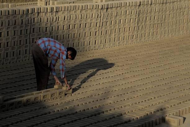 Indian labourer works at a brick kiln in the outskirt of Jalandhar on March 4 2018 / AFP PHOTO / SHAMMI MEHRA