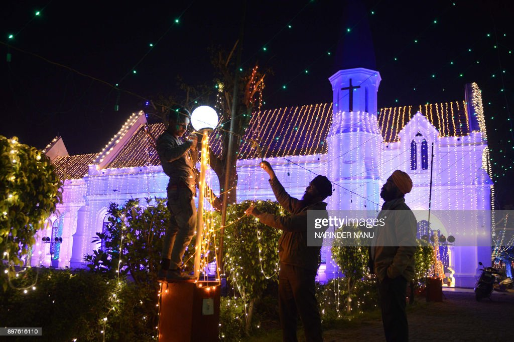 Indian labourers adjust lights at the illuminated St Paul`s Church in Amritsar on December 23 2017 / AFP PHOTO / NARINDER NANU