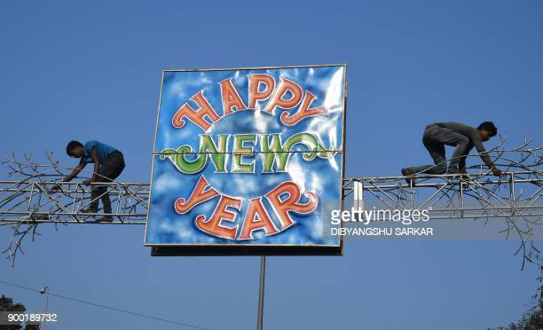 Indian labourers affix a Happy New Year sign over a road in Kolkata on January 1 2018 / AFP PHOTO / Dibyangshu SARKAR