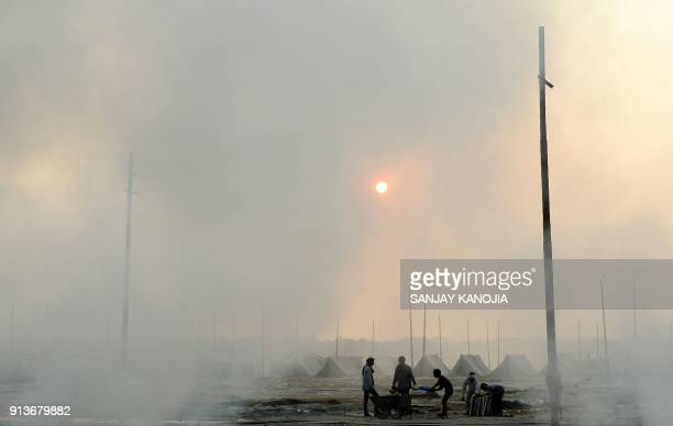 TOPSHOT Indian labourers burn trash following the conclusion of annual Magh Mela festival at Sangam in Allahabad on February 3 2018 / AFP PHOTO /...