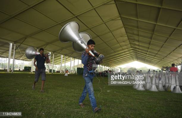 Indian labourers carry audio speakers before connecting the loudspeaker system for a campaign rally to be held by Prime Minister Narendra Modi in the...