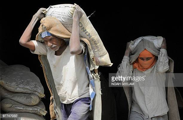 Indian labourers carry bags of cement towards a waiting truck at a warehouse on the outskirts of Hyderabad on March 16 2010 Rising cement sales of...