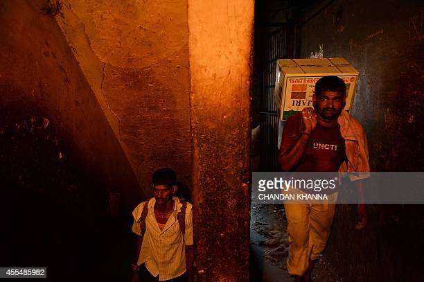 Indian labourers carry cases of goods at a spice market in the old quarters of New Delhi on September 15 2014 The labour sector of the Indian economy...