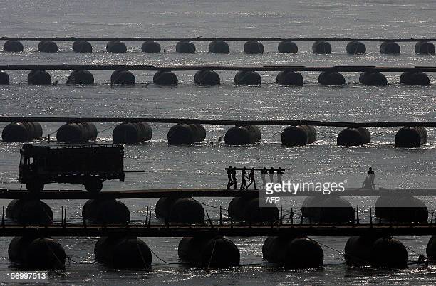Indian labourers carry wood sleepers to construct a temporary pontoon bridge over the River Ganges at Allahabad on November 27 2012 Allahabad located...