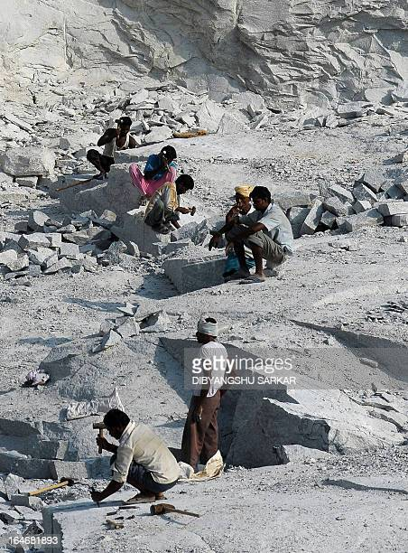 Indian labourers chisel stone at a quarry in Kadaganahalli village on the outskirts of Indian IT capital Bangalore on April 21 2010 Stone quarrying...