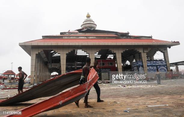Indian labourers clean away debris at a bus stand in Puri on May 5 after Cyclone Fani swept through the area Cyclone Fani one of the biggest to hit...