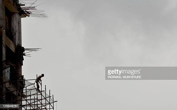 Indian labourers climb up a scaffolding at an underconstruction site of a commercial complex in Mumbai on September 20, 2011. India's benchmark...