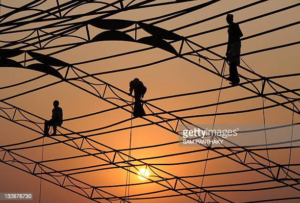 Indian labourers erect a temporary structure in Ahmedabad on November 13 2011 India's central bank which has hiked interest rates 13 times since...