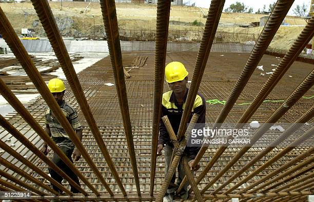 Indian labourers examine a joint in a set of iron rods at a construction for a Prototype Fast Breeder Reactor at the Indira Gandhi Centre for Atomic...