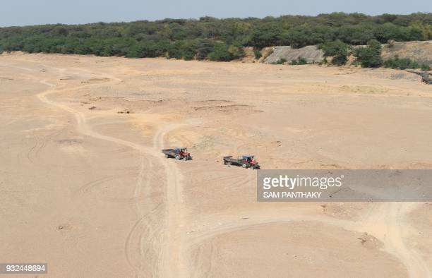 Indian labourers excavate sand from the dry river bed of Sabarmati at Dholakuva village near Gandhinagar some 30 kms from Ahmedabad on March 15 2018...