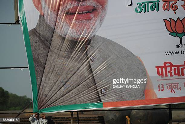 TOPSHOT Indian labourers hang a banner bearing the image of Indian Prime Minister Narendra Modi ahead of the forthcoming Parivartan Rally in...