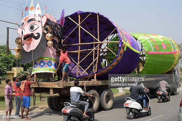 Indian labourers load an effigy of the Hindu demon King Ravana onto a truck on the outskirts of Amritsar on October 8 ahead of the Hindu festival of...