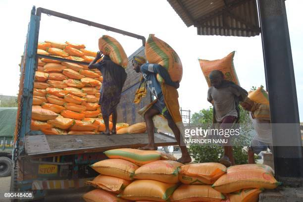 Indian labourers load sacks of fertiliser onto a truck at a railway station on the outskirts of Amritsar on May 31 2017 India's economic growth...