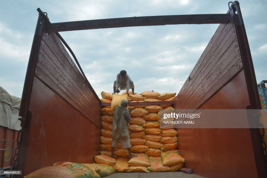 Indian labourers load sacks of fertiliser onto a truck at a railway station on the outskirts of Amritsar on May 31 2017 India`s economic growth...