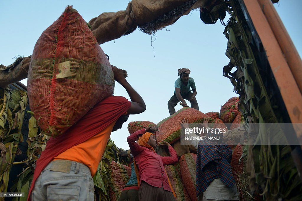 Indian labourers load sacks of peas into a truck at a wholesale vegetable market on the outskirts of Amritsar on December 5 2016 / AFP / NARINDER NANU