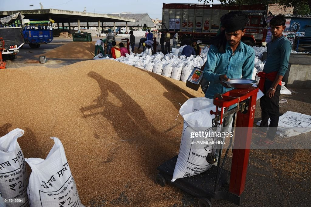 Indian labourers pack wheat grain at a market in Jalandhar in northern Punjab state on April 17 2018 Scores of debtladen farmers in India have...