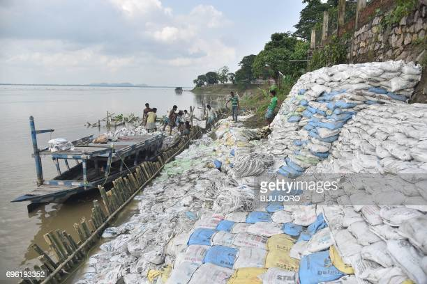 Indian labourers pile up sand bags as they work to build up a bank of the River Brahmaputra to protect it from erosion in Guwahati on June 15 2017 /...
