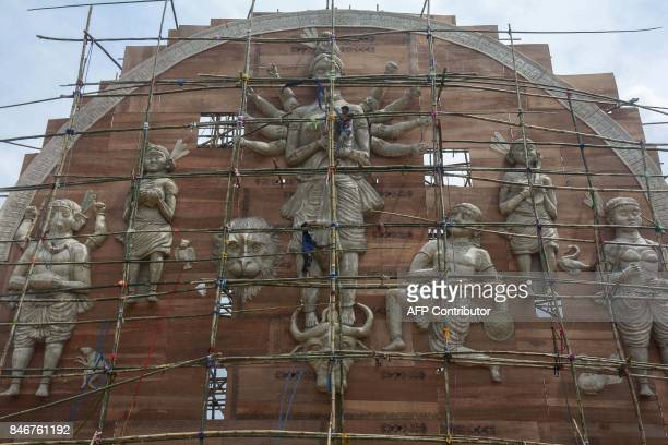 Indian labourers prepare a large idol of the Hindu goddess Durga ahead of the Durga Puja festival in Agartala the capital of northeastern state of...