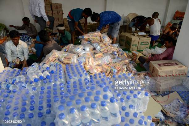 Indian labourers prepare food aid from Punjab state government to be shipped to floodhit Kerala in Jalandhar on August 19 2018 Rescuers waded into...