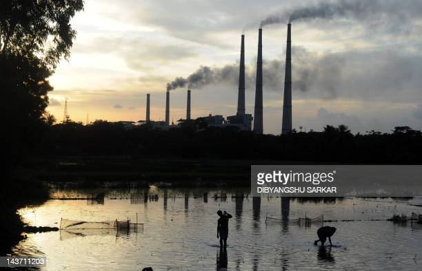Indian labourers prepare the flooded field for rice farming as chimneys of Kolaghat Thermal Power Plant are seen in the background in Mecheda around...