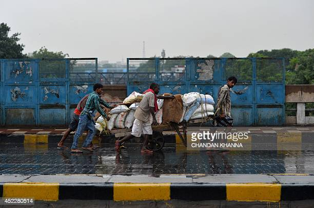 Indian labourers pull a hand loaded with sacks as rain falls in New Delhi on July 17 2014 Rain fell in several areas of northern India bringing down...