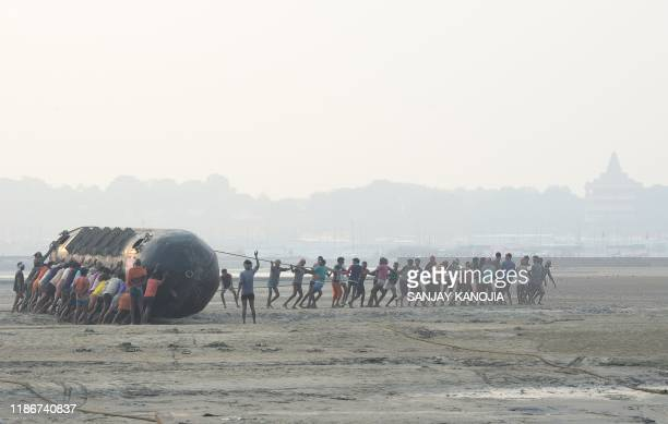Indian labourers pull a pontoon buoy with ropes in the banks of the Ganges River as they build floating bridges for the upcoming Hindu festival of...