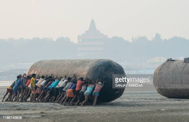 TOPSHOT Indian labourers push a pontoon buoy in the banks of theGanges River as they build a floating bridges for the upcoming Hindu festival of Magh...