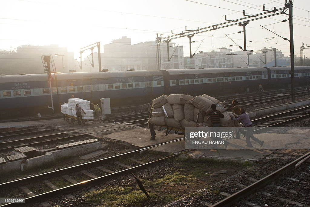 Indian labourers push carts filled with goods past railroad tracks at the Hazrat Nizamuddin railway station in New Delhi on February 26, 2013, when the railway budget is due to be tabled in Parliament. The railway, the country's largest employer with some 1.4 million people on its payroll, runs 11,000 passenger and freight trains and carries 19 million people daily.