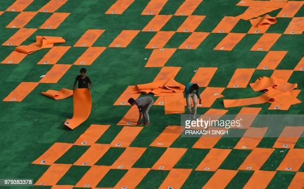 Indian labourers rearrange yoga mats at Forest Research Institute ground after a sudden shower on the eve of International Yoga Day in Dehradun on...