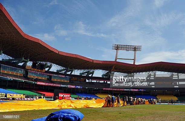 Indian labourers remove the plastic covers from the grounds ahead of the first One Day International cricket match between India and Australia at the...