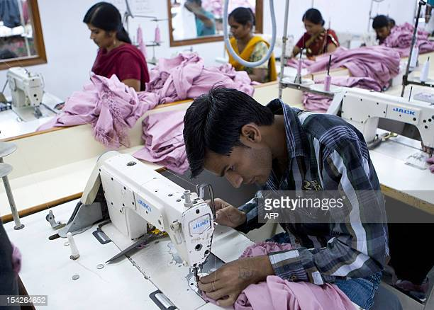 Indian labourers sew dresses at the April Cornell clothing factory in Noida on the outskirts of New Delhi on October 16 2012 The April Cornell...